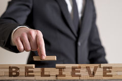 Man assembling word Believe. Front view of a businessman in suit building a structure of wooden bricks while assembling word Believe Stock Images