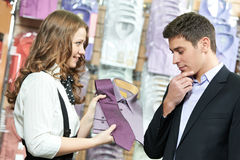 Man and assistant at apparel. Young men choosing shirt and necktie during apparel shopping at clothing store royalty free stock photography