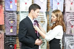 Man and assistant at apparel clothes shopping. Young men choosing shirt and necktie during apparel shopping at clothing store stock photos