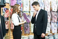 Man and assistant at apparel clothes shopping. Young men choosing shirt and necktie during apparel shopping at clothing store Royalty Free Stock Photography