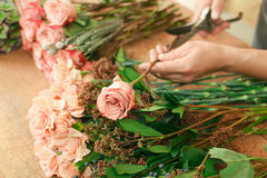 Man assistant in flower shop delivery make rose bouquet closeup. Flowers delivery, creating order. Male florist hands closeup, cuts rose for bouquet in flower royalty free stock image