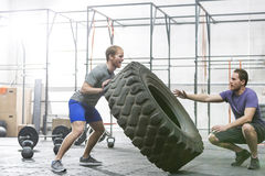 Man assisting at dedicated friend in flipping tire at crossfit gym stock photos