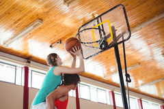 Man assisting female friend while playing basketball Stock Photo