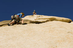 Man Assisting Friend Climbing Rock Against Blue Sky Stock Images