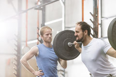 Man assisting friend in lifting barbell at crossfit gym Stock Images