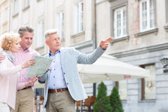 Man assisting to middle-aged couple with road map in city Stock Photo