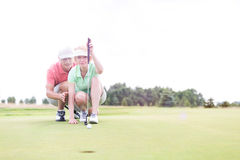 Man assisting woman aiming ball on golf course against clear sky Stock Images
