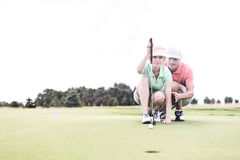 Man assisting woman aiming ball on golf course against clear sky. Man assisting women aiming ball on golf course against clear sky stock images