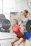 Man assisting woman in lifting barbell in crossfit gym Stock Photography