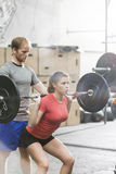 Man assisting woman in lifting barbell in crossfit gym Stock Photo