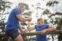 Man assisting woman to climb a hurdles during obstacle training Royalty Free Stock Images