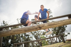 Man assisting woman to climb a hurdles during obstacle training Stock Photos