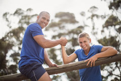 Man assisting woman to climb a hurdles during obstacle training Royalty Free Stock Image