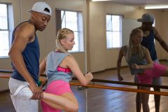 Man assisting female friend in stretching leg on barre Royalty Free Stock Photography