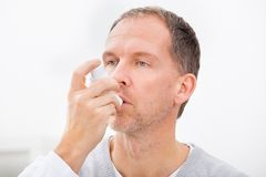 Man with asthma inhaler. Man With Asthma Using An Asthma Inhaler For Preventing Attacks royalty free stock images