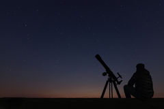 Man with astronomy telescope looking at the stars. Man telescope and starry sky. Night sky. Milky way galaxy stock photo
