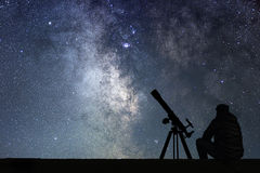 Man with astronomy  telescope looking at the stars. Stock Photo