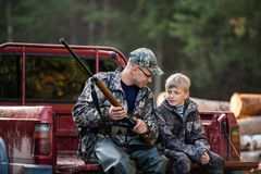 Free Man At His Truck With His Son In The Forest. Hunter Teaches Young Boy How To Use Shotgun Rifle. Stock Photography - 162892942