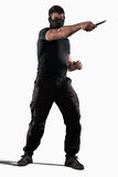 Man atacking with knife isolated. Man in black uniform attacking with knife isolated on white royalty free stock photo