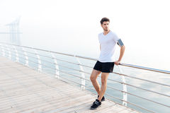 Man athlete with armband and cell phone standing on pier. Attractive young man athlete with armband and cell phone standing on pier royalty free stock photo