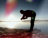 Man athlete checking time during workout run exercise at ocean beach in sunny morning. Royalty Free Stock Image