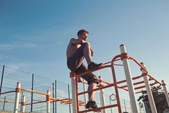 Man athlete climb on metal jungle gym on blue sky. Sportsman with bare torso on monkey bars top. Macho relax after. Workout outdoor. Sport health and energy royalty free stock images
