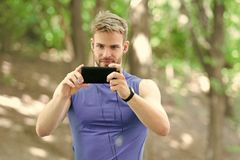Man athlete concentrated face take smartphone photo nature background. Sportsman training pedometer and headphones. Gadgets. Athlete bristle fitness tracker and royalty free stock image