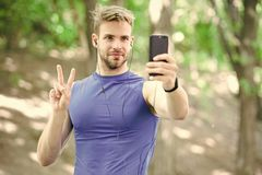 Man athlete concentrated face take smartphone photo nature background. Sportsman take photo winner sport competition. Athlete fitness tracker and smartphone royalty free stock photos