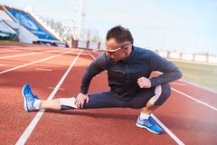 Man athlete doing stretching on the track at the stadium. For any purpose Royalty Free Stock Images