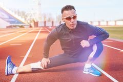 Man athlete doing stretching on the track at the stadium. For any purpose Stock Photography