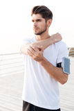 Man athlete with mobile phone in armband stretching arms Royalty Free Stock Image