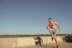 Man athlete muscular torso training outdoor. Morning run fills with energy. Runner training morning during sunrise. Motivation and achievement. Run morning royalty free stock photography