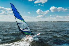 The man athlete rides the windsurf over the waves on lake. The man athlete rides the windsurf over the waves on the lake stock images