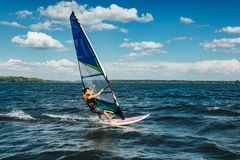 The man athlete rides the windsurf over the waves on lake. The man athlete rides the windsurf over the waves on the lake stock photo