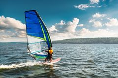 The man athlete rides the windsurf over the waves on lake. The man athlete rides the windsurf over the waves on the lake stock image