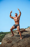 Man Athlete on a rock by the sea against the sky Stock Photo
