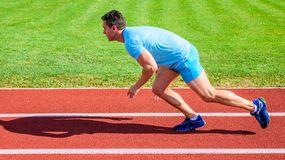 Man athlete runner push off starting position stadium path sunny day. Runner captured in motion just after start of race. Runner sprint race at stadium. How to stock images