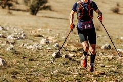 Man athlete runner running mountain trail. With trekking poles Royalty Free Stock Images