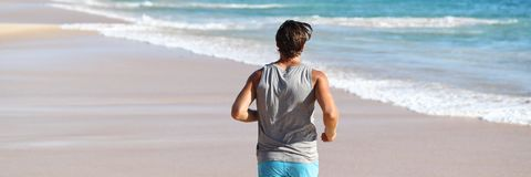 Man athlete running on beach at sunset banner. Man athlete running away from behind on beach . Male runner doing cardio exercise workout on sand. Healthy active stock photo