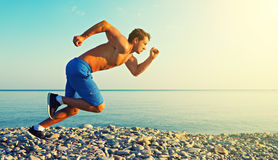 Man athlete running by  sea at sunset outdoors Stock Images