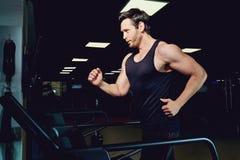 Man athlete runs jogging on a treadmill in dark gym.  Royalty Free Stock Photos