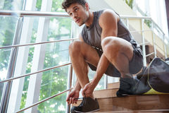 Man athlete sitting and tying laces on stairs. Handsome young man athlete sitting and tying laces on stairs Stock Photos