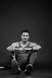 Man athlete sportsman, prosthetic leg. One disabled young adult man, prosthetic leg, athlete, sitting on floor, black background, sportsman Royalty Free Stock Photos