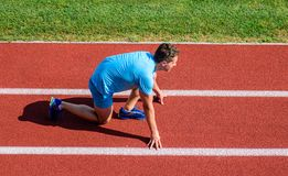 Man athlete stand low start position at stadium path. Beginning of new lifestyle habit. Runner ready to go. Athlete royalty free stock photography