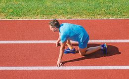 Man athlete stand low start position at stadium path. Beginning of new lifestyle habit. Runner ready to go. Athlete. Runner prepare to race at stadium. How to royalty free stock photo
