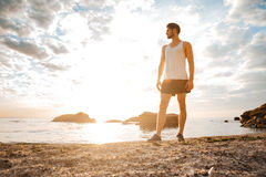 Man athlete standing with arms raised and looking at sunset Stock Photography