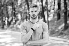 Man athlete on strict face posing with sportive equipment, nature background. Athlete with bristle with fitness tracker. Or pedometer. Sport gadget concept royalty free stock photos
