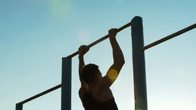 Man athlete training on chin-up bars outdoors, physical strength and sport stock images