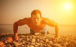 Man athlete trains, practicing, on the beach. Man athlete trains, practicing, playing sports pushed on the nature on the beach stock photo