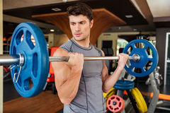 Man athlete working out with barbell in gym Stock Images